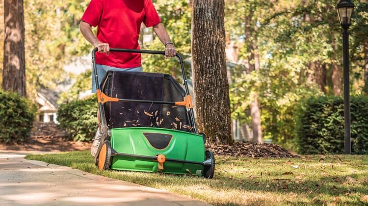 Man using one of the best lawn sweepers for a clean yard