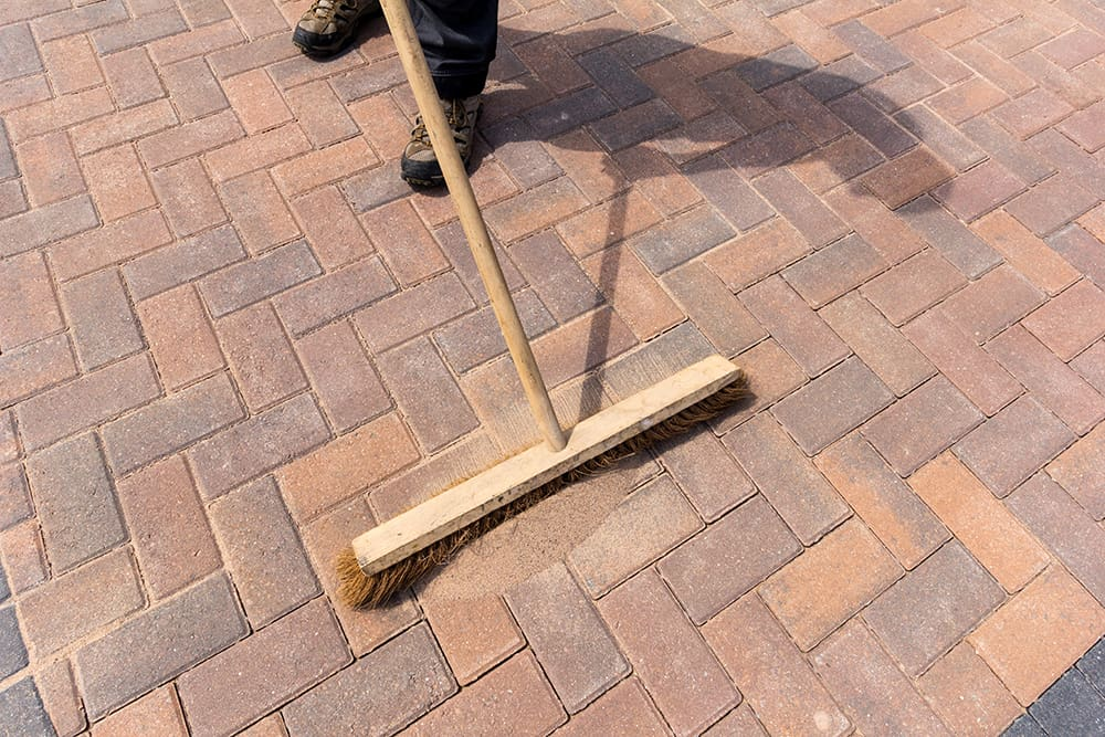 Man laying joint sand between pavers to prevent weeds from growing