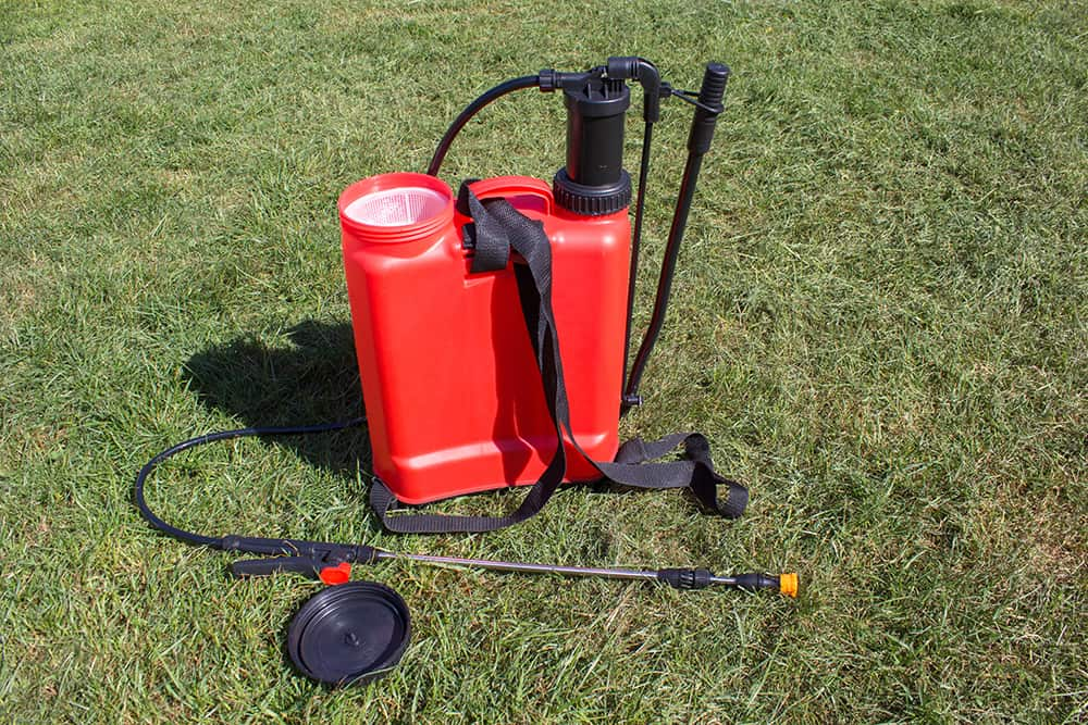 A spraying backpack for applying liquid pre-emergent weed killer to a lawn