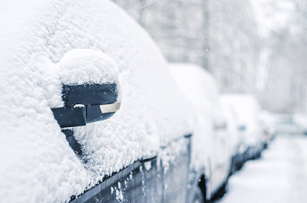Cars parked outside with snow covering the windows
