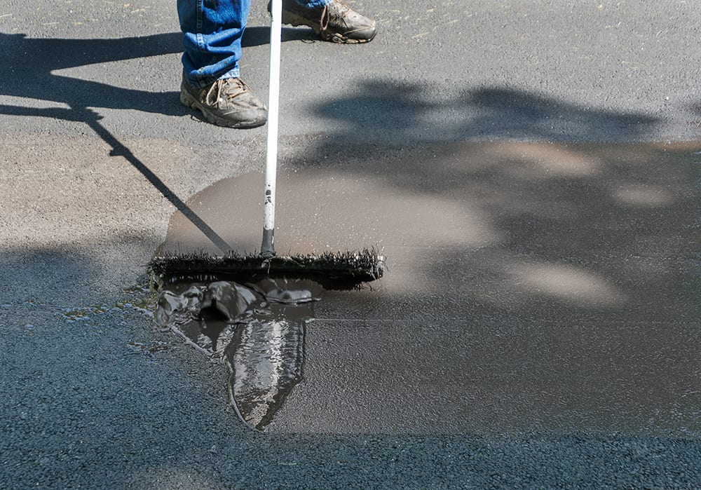 Man sealing driveway before rain, leaving at least 4-8 hours to dry before rainfall.