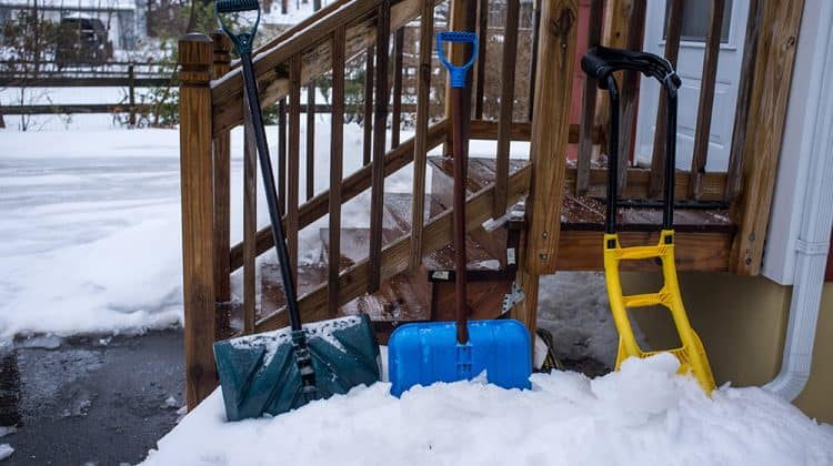 Pair of shovels used to clear snow and ice off wooden steps