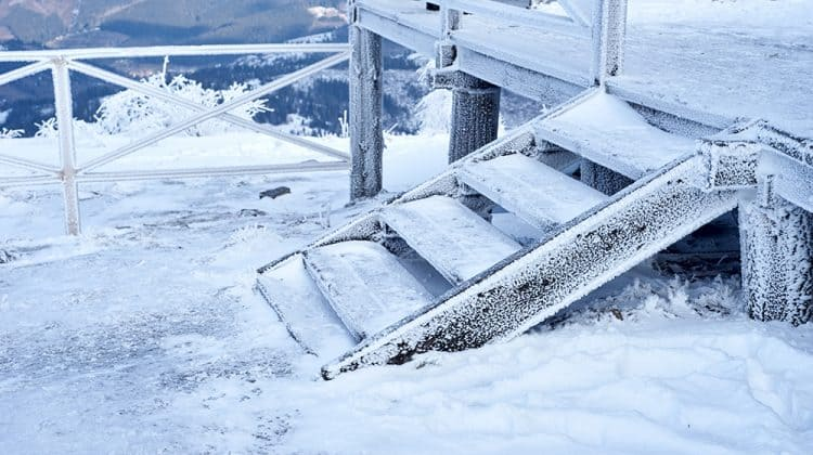 Snow and ice on wooden stairs leading up to a house