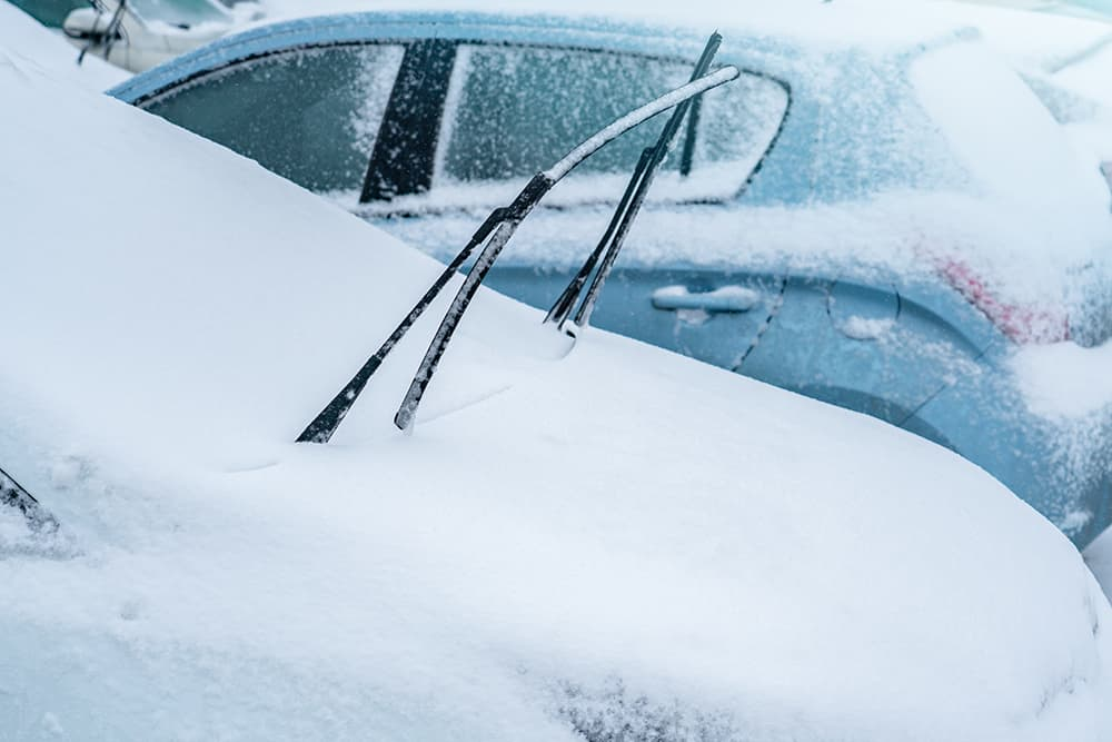 Car parked outside in snow with wiper blades standing up to help de-ice the window and prevent any additional ice or frost damage