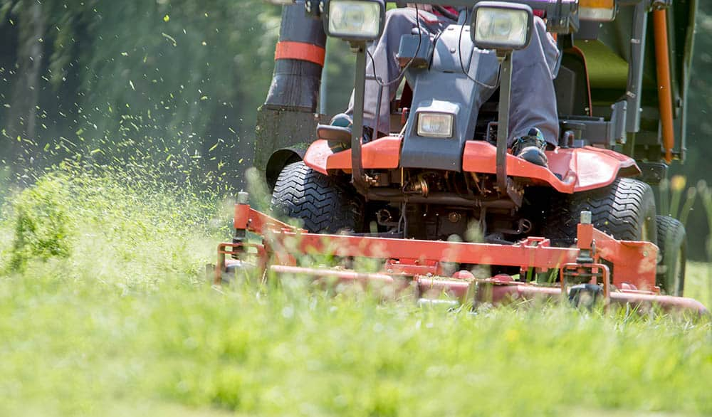 Man cutting tall grass with a riding lawn mower
