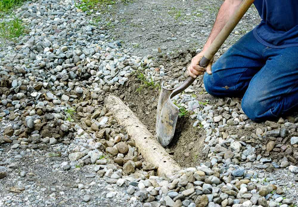 Man installing french drain