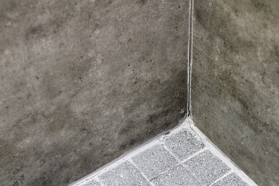 Can you caulk over grout in shower corners?