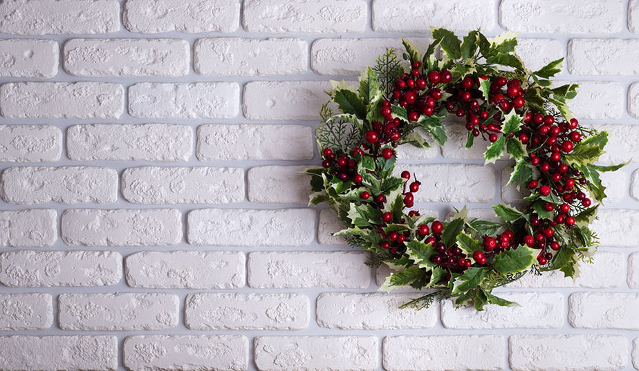 Decorate your wreath after hanging it on a brick wall