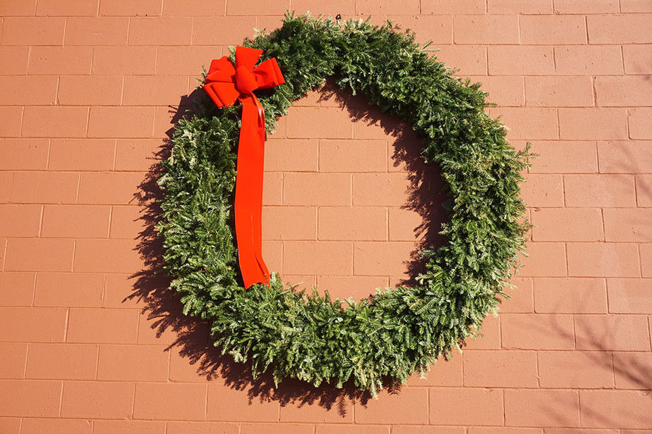 Hanging a wreath on a brick wall outside