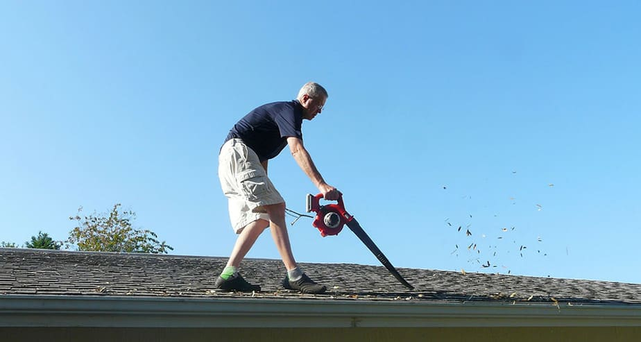 Man blowing leaves from his roof in the spring on a day without any wind