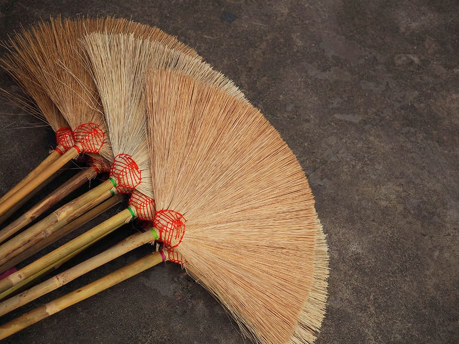 Try a straw broom to clean leaves from rocks
